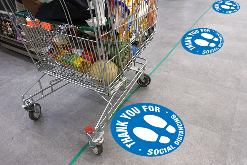 Social distancing floor decals at a grocery store